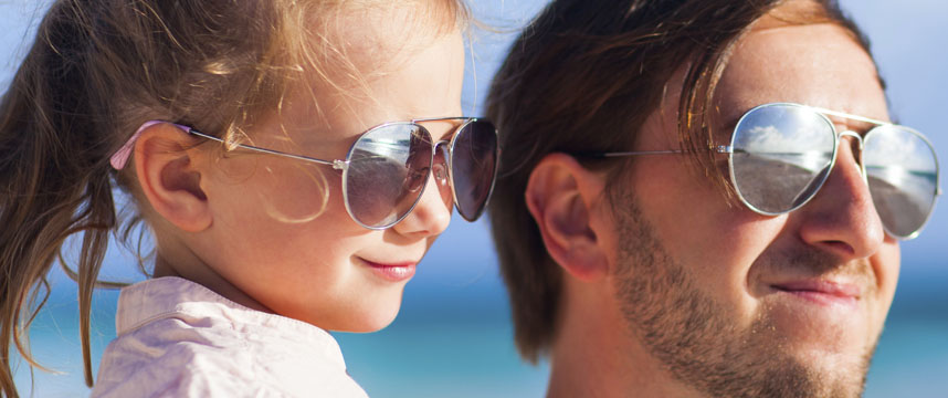 A father and daughter wearing glasses, looking at an ocean sunset